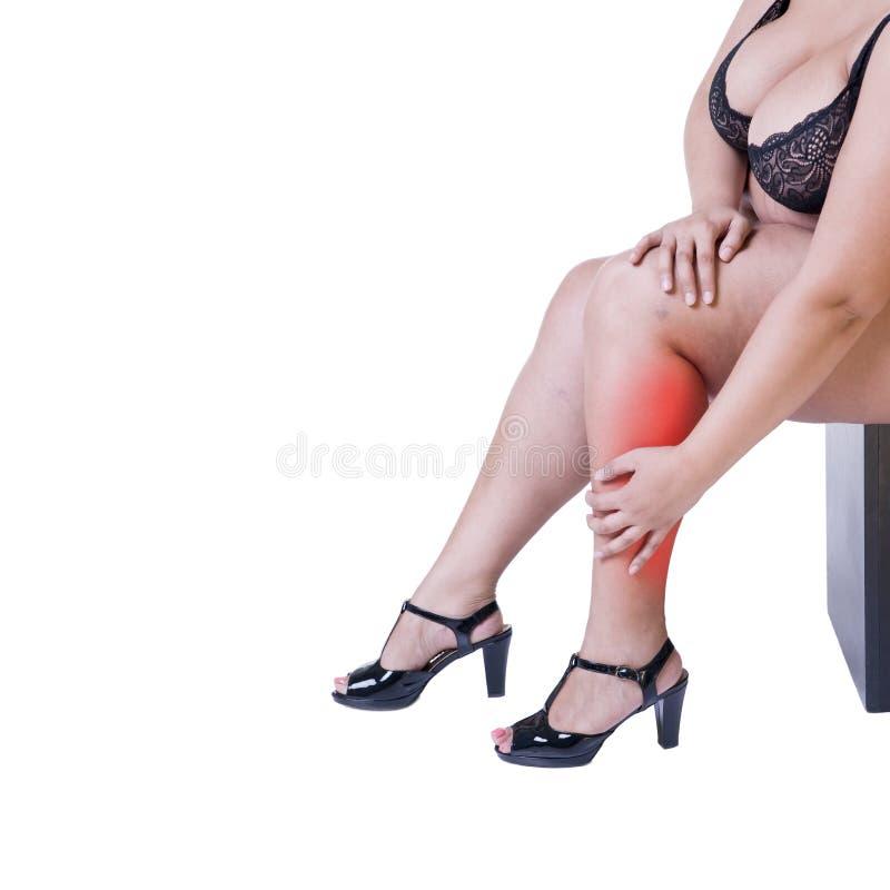 Dolore di gamba, donna grassa con il dolore del muscolo, ente femminile di peso eccessivo isolato su fondo bianco immagini stock
