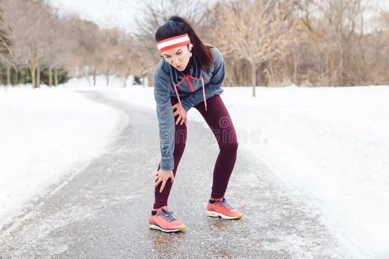 Dolore di sensibilità della giovane donna in gambe dopo avere pareggiato fuori nel parco di inverno immagini stock libere da diritti