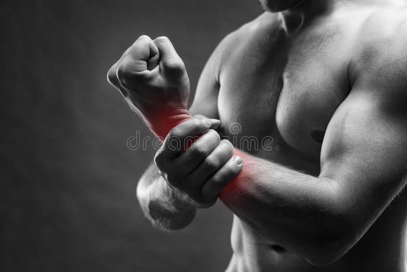 Dolore nella mano Ente maschio muscolare Culturista bello che posa sul fondo grigio immagine stock libera da diritti