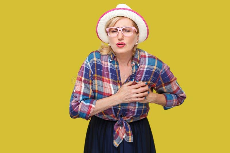 Dolore o infarto di attacco di cuore Ritratto della donna matura nello stile casuale con il cappello, condizione degli occhiali,  fotografia stock libera da diritti