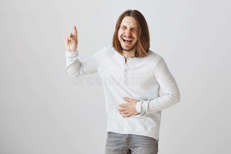 Dolores de vientre de la risa hacia fuera ruidosamente Retrato del individuo hermoso feliz contento con la barba y el pelo justo  fotografía de archivo libre de regalías