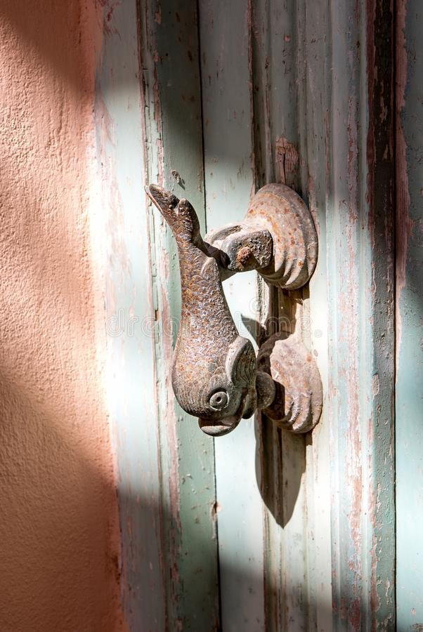 Dolphin door handle, a detail of Rethymno old town, Crete island, Greece. Dolphin is symbol of Greece and particular Crete island stock photography