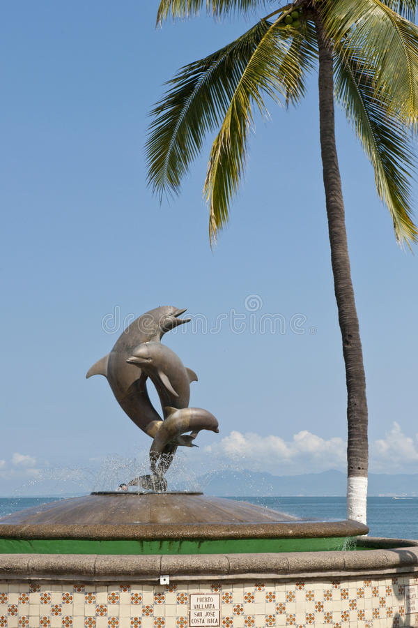 Dolphin statue and palm tree