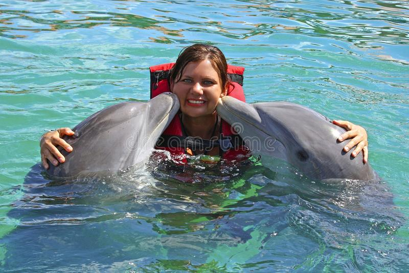 Dolphins kissing young girl, Cuba stock photo
