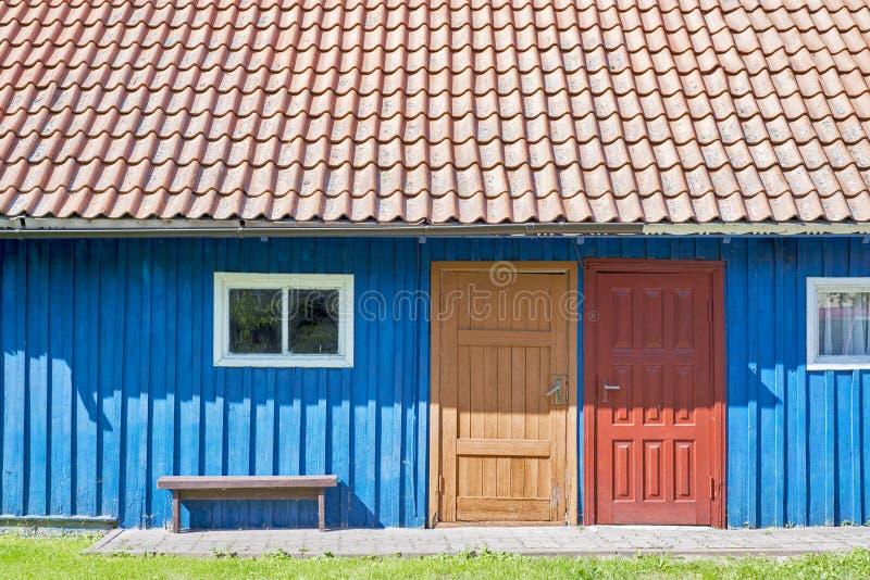 Dom błękitne drewniane deski, czerwień dach, dwa kolorowego drzwi i małych okno, zdjęcie royalty free