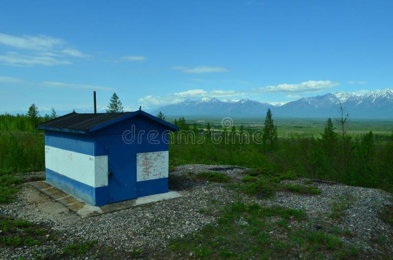 Dom dla linia kolejowa pracowników grzać Las, niebo, śnieżne góry zdjęcia stock