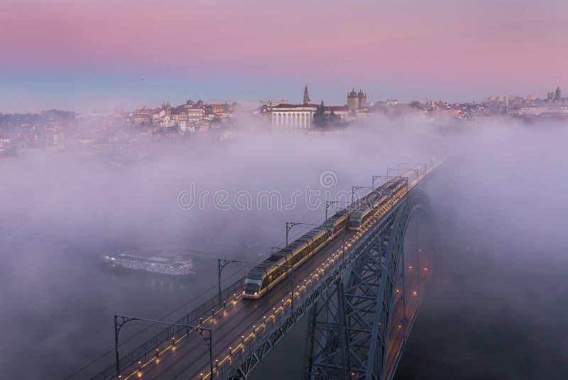 Dom famosos Luis de Ponte del puente cubierto con niebla de la mañana durante salida del sol en Oporto imagen de archivo