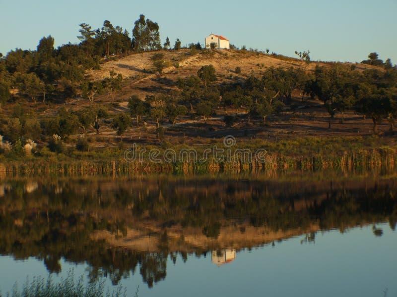 Dom i góra odbijający w wodzie zdjęcia stock