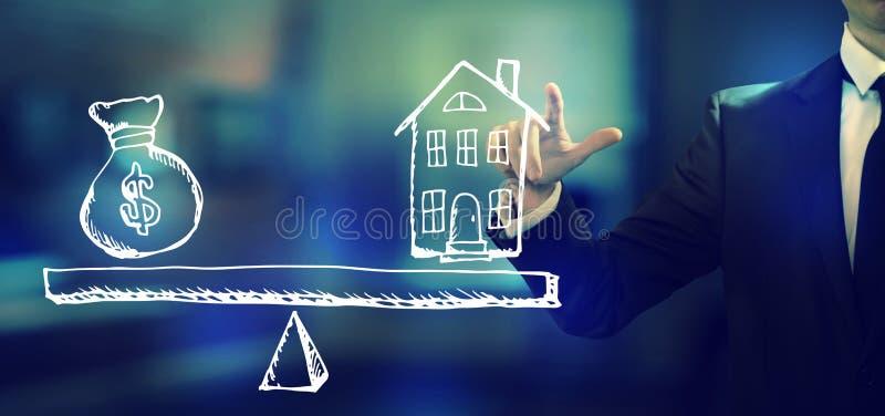 Dom i pieniądze na skali z biznesmenem zdjęcia royalty free