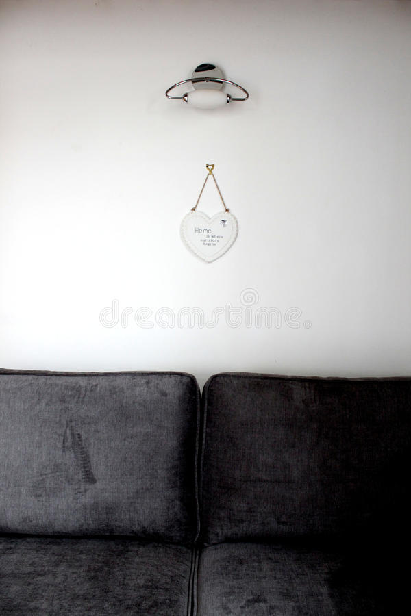 ` dom jest dokąd opowieść zaczyna ` znaka na biel ścianie pod ścianą lekką i nad pluszowego zmroku popielata miękka kanapa fotografia stock
