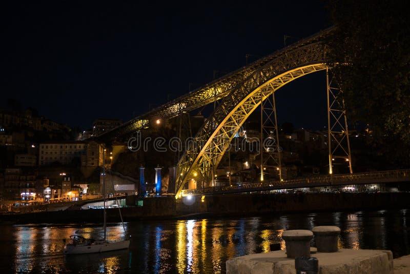Dom Luis Bridge och fartyg i floden Douro i Porto, Portugal på solnedgången med ljus reflekterade i floden royaltyfria foton