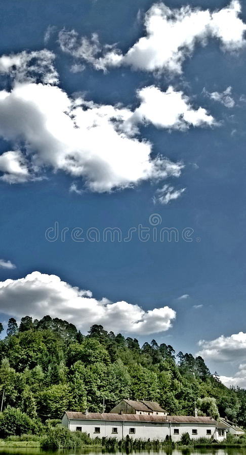 Dom na jeziorze z niebieskim niebem i bielem chmurnieje zdjęcie stock