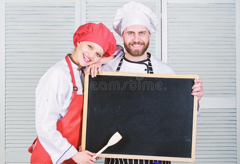 Dom?nio cozinhando habilidades Pares de homem e de mulher que guardam o quadro-negro vazio em cozinhar a escola Cozinheiro mestre imagem de stock