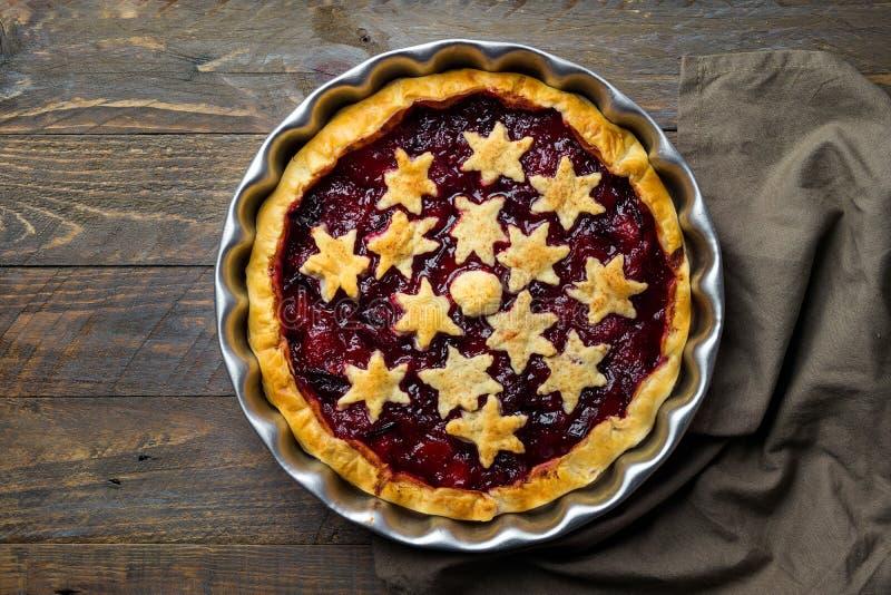 Dom piec ptysiowego ciasta Bożenarodzeniowy tarta z śliwkowym cynamonowym dżemu plombowaniem dekorował z gwiazdami Ciemny drewnia obraz stock