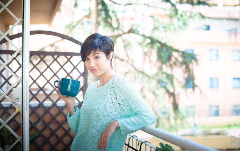 Dom relaksuje, młoda kobieta pije kawę obrazy stock