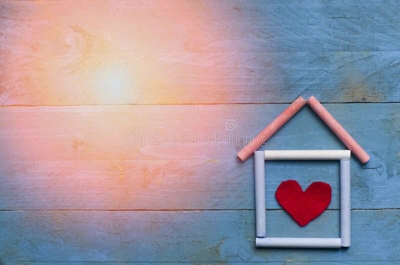 Dom robić kreda z słońcem na błękitnym drewnianym tle obrazy royalty free