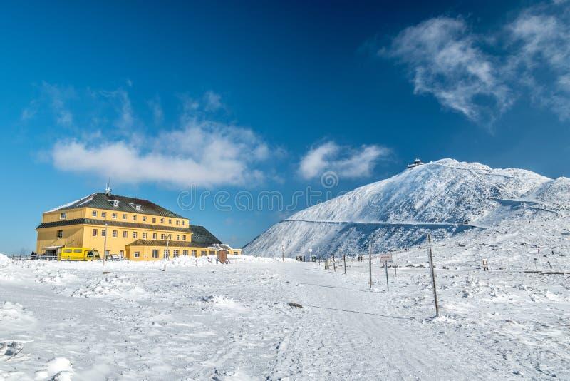 Dom van Slezsky dum Slaski berghut met Snezka-piek binnen erachter op een zonnige dag in de winter, Krkonose-bergen, Polen-Tsjech stock foto