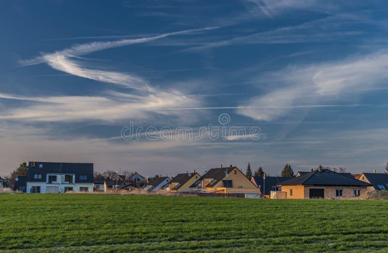 Domaines de la couleur et ciel bleu dans le temps de coucher du soleil près de Ceske Budejovice avec de nouvelles maisons photos stock