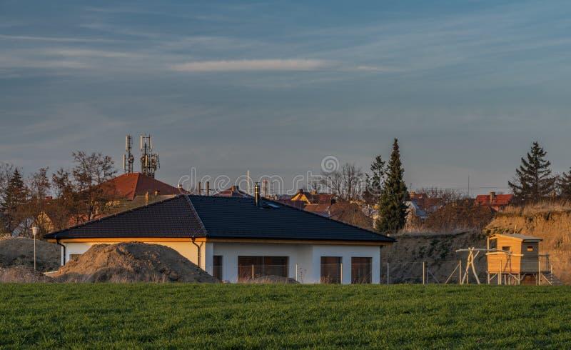 Domaines de la couleur et ciel bleu dans le temps de coucher du soleil près de Ceske Budejovice avec de nouvelles maisons photographie stock libre de droits