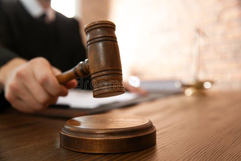 Domare med auktionsklubban på tabellen i rättssalen, closeup arkivbilder