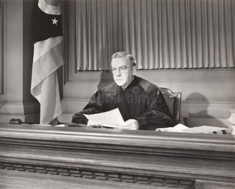 Domare som rymmer ett dokument i rättssal arkivfoton