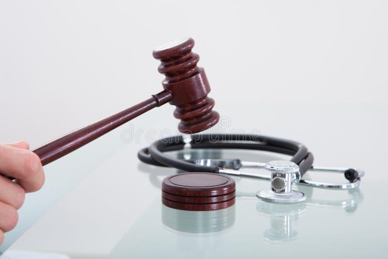 Domareauktionsklubba och en stetoskop i en begreppsmässig bild arkivfoto