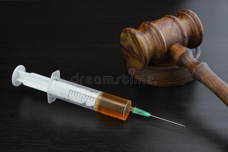 Domareauktionsklubba och läkarundersökninginjektioninjektionsspruta på svarta träBackg arkivfoton