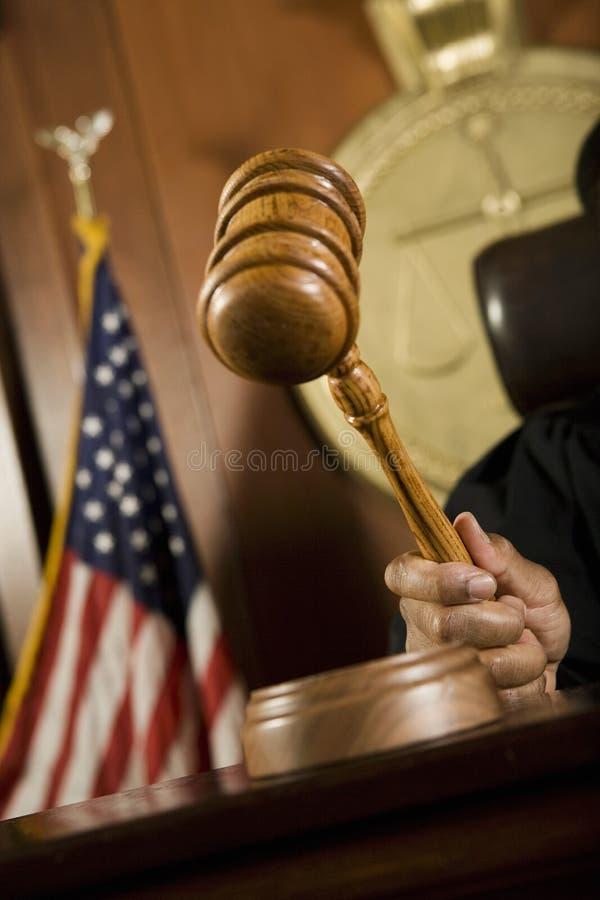 DomareStriking Gavel In rättssal royaltyfri bild