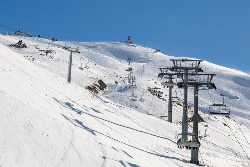 Chairlift lifts skiers and snowboarders to the top of the mountain in a winter sunny day royalty free stock images