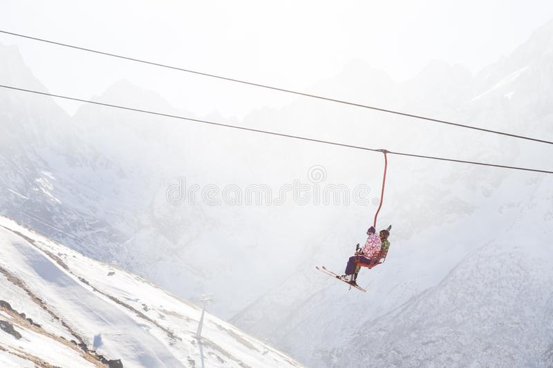 DOMBAI, RUSSIA - JANUARY 3, 2014: People are lifting on open lft high up in Caucasus mountains. DOMBAI, RUSSIA - JANUARY 3, 2014: People are lifting on ski lift royalty free stock photography