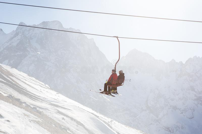 DOMBAI, RUSSIA - JANUARY 3, 2014: People are lifting on open lft high up in Caucasus mountains. DOMBAI, RUSSIA - JANUARY 3, 2014: People are lifting on ski lift royalty free stock photos