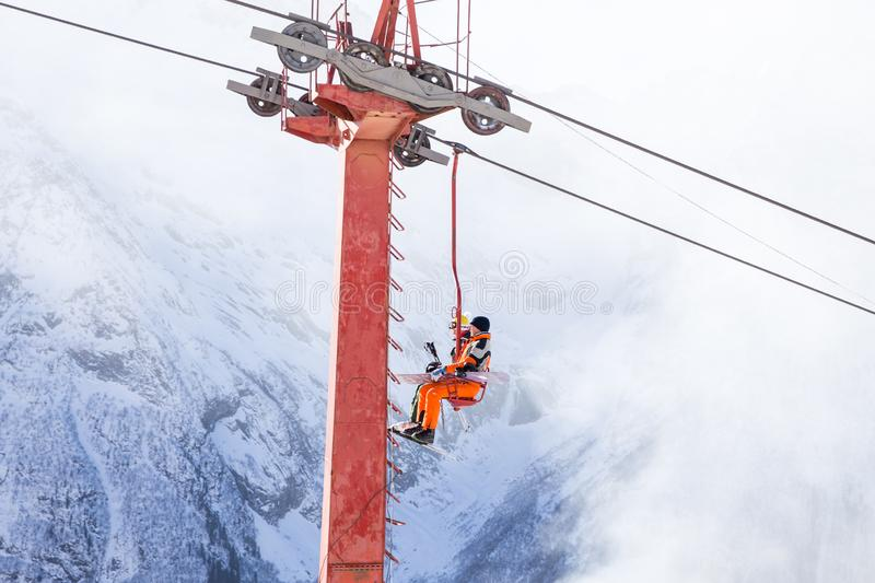 DOMBAI, RUSSIA - JANUARY 3, 2014: People are lifting on open lft high up in Caucasus mountains. DOMBAI, RUSSIA - JANUARY 3, 2014: People are lifting on ski lift royalty free stock images