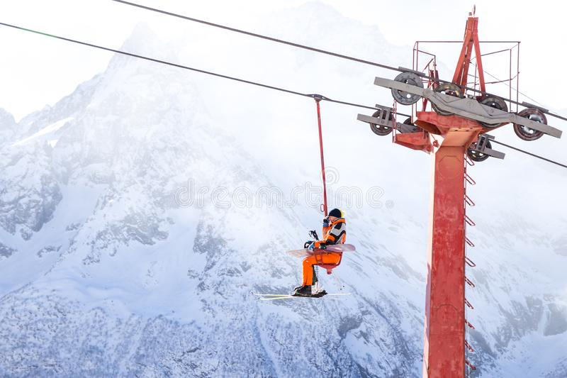 DOMBAI, RUSSIA - JANUARY 3, 2014: People are lifting on open lft high up in Caucasus mountains. DOMBAI, RUSSIA - JANUARY 3, 2014: People are lifting on ski lift stock image