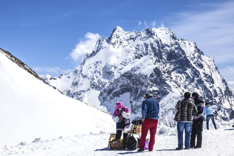 Dombay. Mountain. Tea party. DOMBAY, RUSSIA - May 03.2015: Tourists buy drinks at the top of the mountain in the climate ski resort Dombay stock image