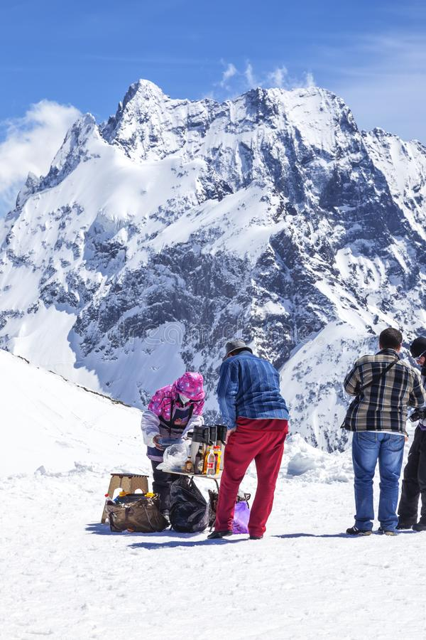 Dombay. Mountain. Tea party. DOMBAY, RUSSIA - May 03.2015: Tourists buy drinks at the top of the mountain in the climate ski resort Dombay stock photo