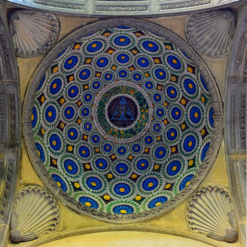Inside of a dome. Dome with blue and yellow abstract round mosaic with four stone shells in corners in the church royalty free stock photo