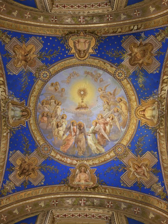Dome ceiling Painting of Eucharist Adoration of the angels. Monstrance with Blessed Sacrament surrounded by archangels and cherubs with Latin text royalty free stock image