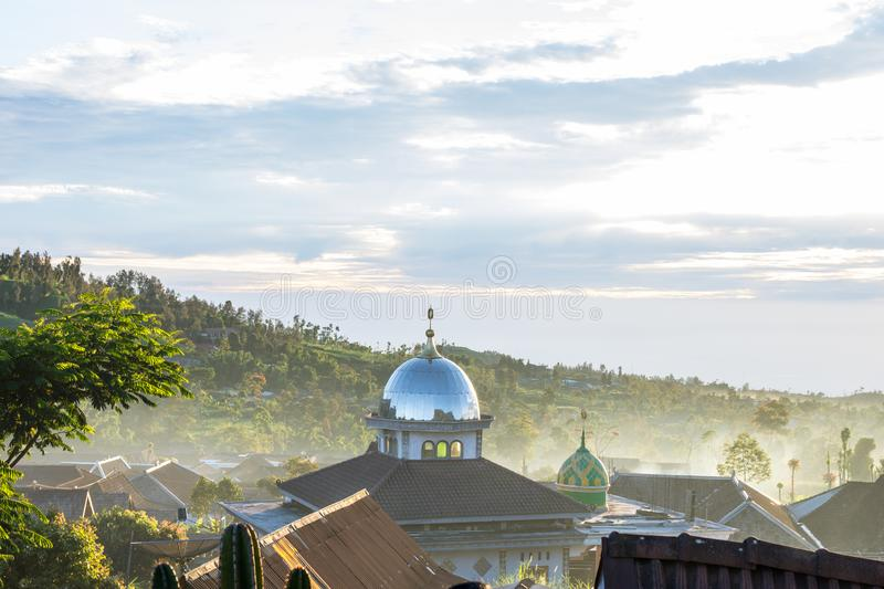 Dome of a mosque and large mountain rising up into the sky with clouds stock photos