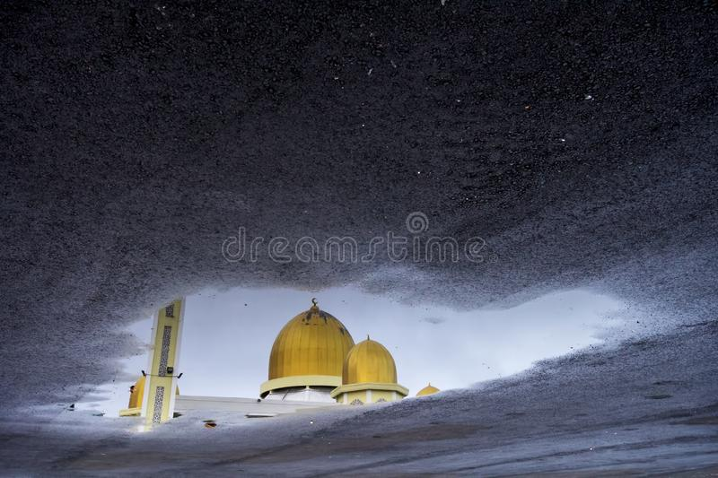 A dome of a mosque reflection on a water. A reflection of a mosque`s dome on a water, the mosque is located in a town of Gua Musang, in a state of Kelantan stock images