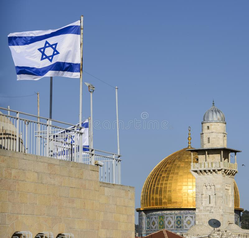 The dome of the rock and a mosque with an israeli flag, jerusalem, israel royalty free stock photography