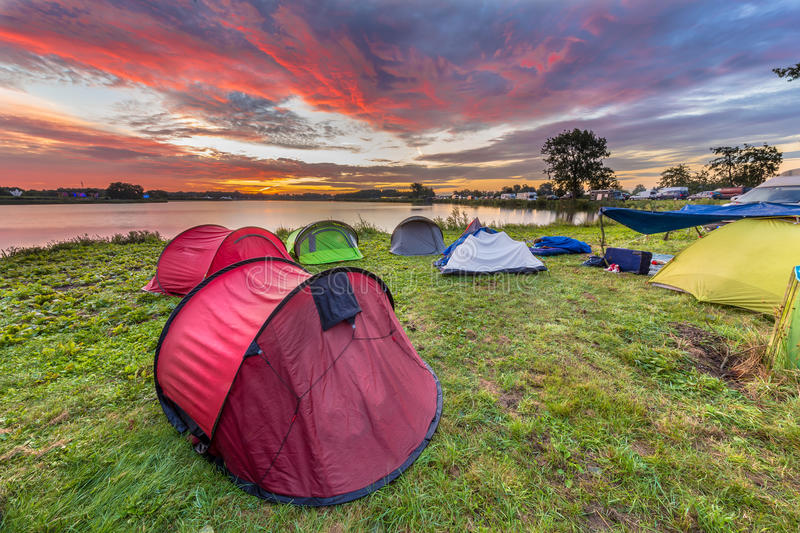 Dome tents camping near lake. On a music festival camp site under beautiful sunrise royalty free stock image