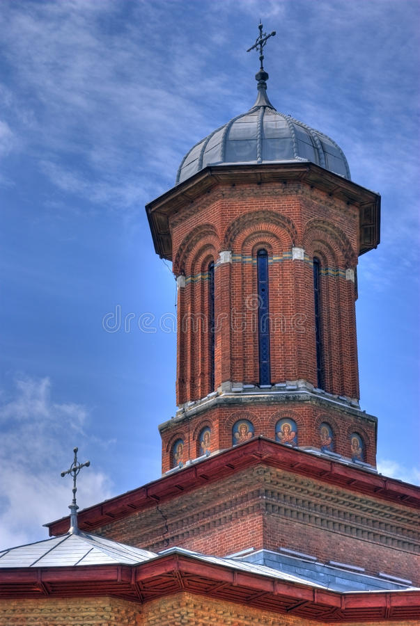 Domed church tower. Architectural detail of domed church tower with blue sky and cloudscape background, Craiova, Romania royalty free stock image