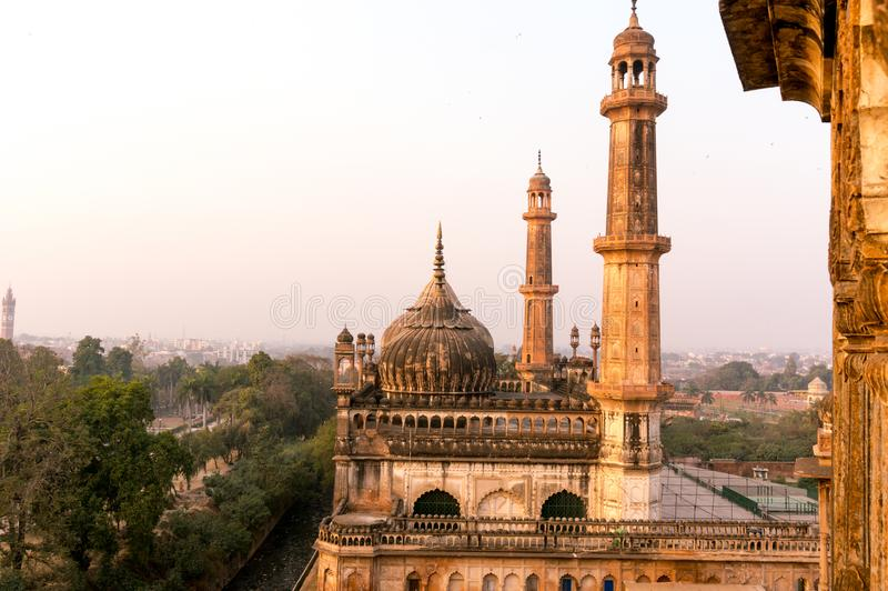 Domed roof and towers of Asfi mosque shot at sunset. From the rooftop of bara imambara in lucknow uttar pradesh india. This marvel of mughal architecture is a stock photo
