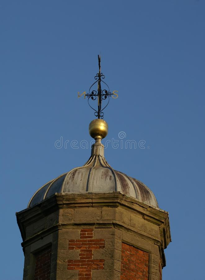 Domed tower with a weather vane. Domed tower with a golden ball and an ornamental weather vane royalty free stock photography