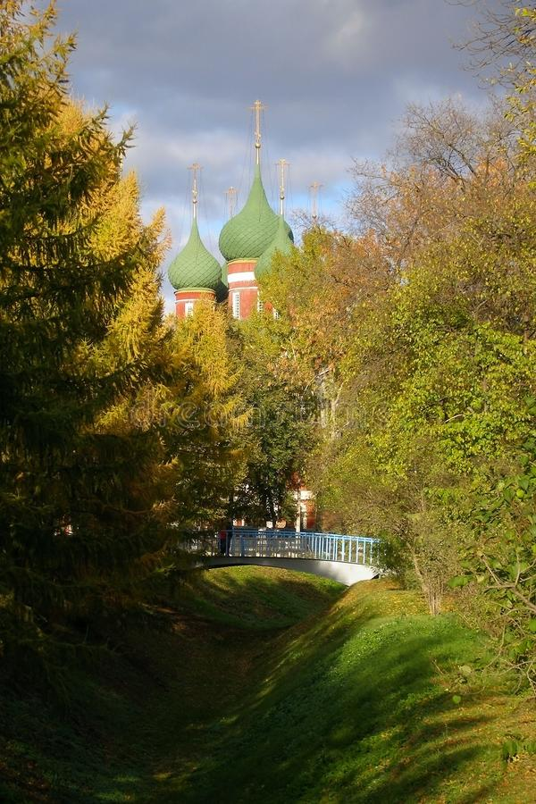 Domes of the church of Archangel Michael. Trees with yellow leaves, bridge over the ravine. Golden autumn Indian summer in Yaros. Lavl, Russia royalty free stock photography