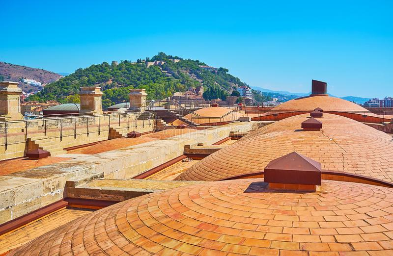 The domes of Malaga Cathedral, Spain. The domes of Malaga Cathedral in front of the green city hill with medieval Gibralfaro Castle, Spain royalty free stock photography