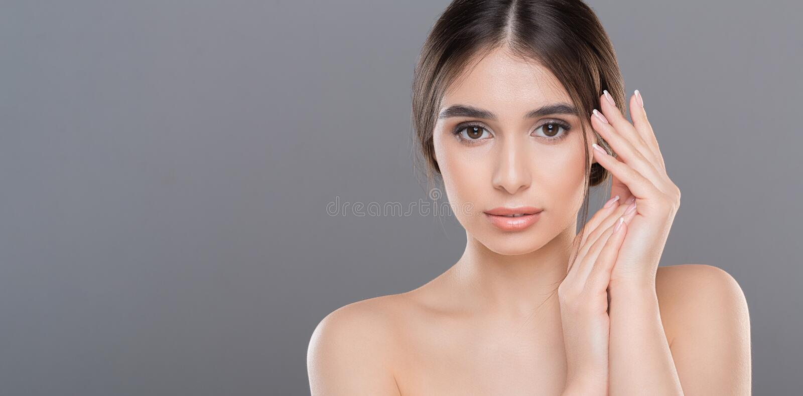 Young woman pampering her hands with lotion. Domestic beauty procedure. Young woman pampering her hands with lotion, panorama with empty space royalty free stock image