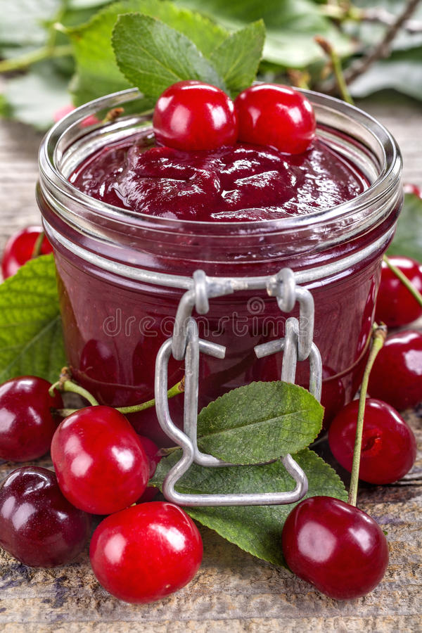 Domestic cherry jam. Domestic fresh cherry jam on a rustic wooden board stock photo