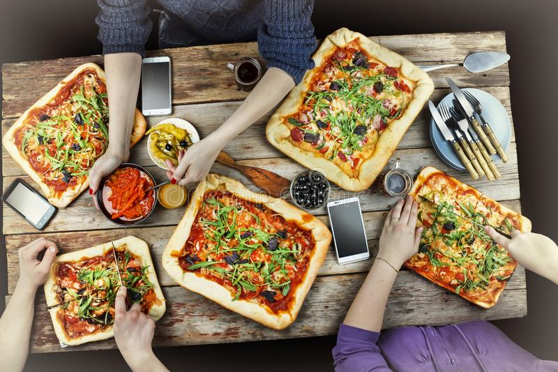 Cutting pizza. Domestic food and homemade pizza. Enjoying dinner with friends. Top view of group of people having dinner together. Domestic food and homemade stock image