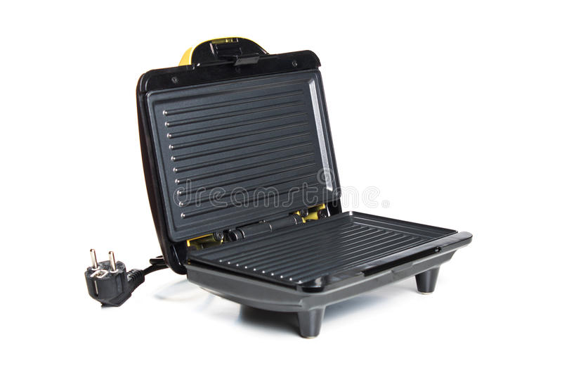 Domestic generic electric panini maker, angled view with the hinged lid partially open to reveal the cast iron plates inside, iso. Lated on white stock photo